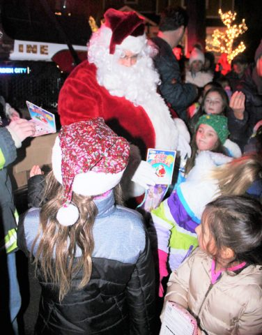 Santa arrives by fire truck to the squeals of the children, and he brings them goodies and good cheer.